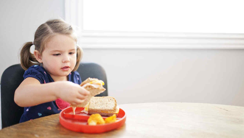 Niña comiendo un sandwich