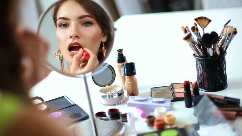 Mujer viéndose al espejo mientras se maquilla