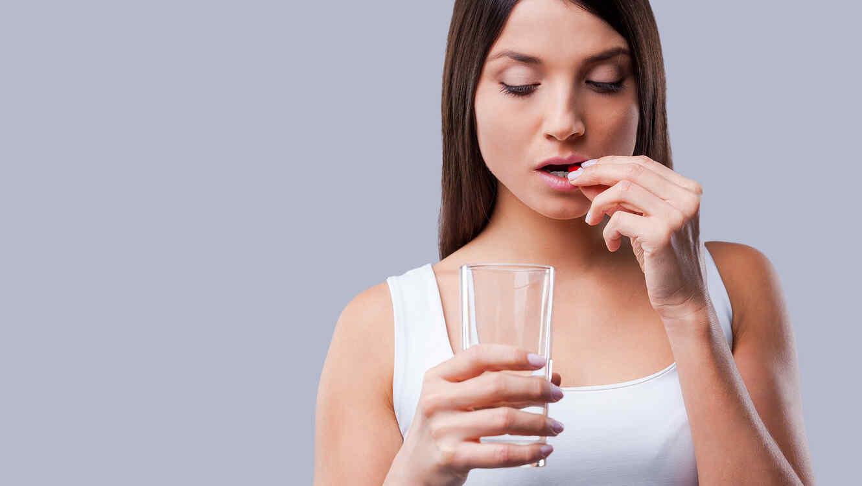 Mujer con vaso de agua toma píldora