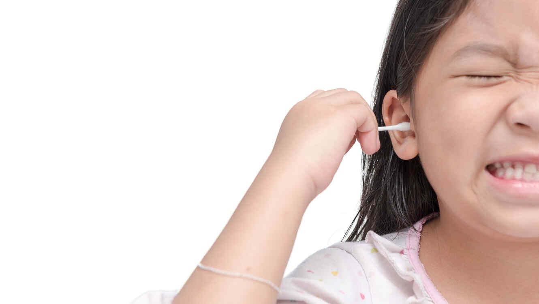 Niña limpia su oído con hisopo de algodón