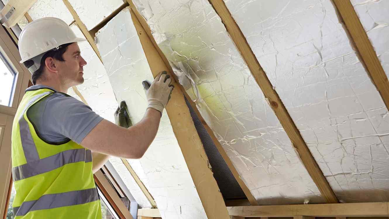 Trabajador colocando aislamiento térmico en una pared