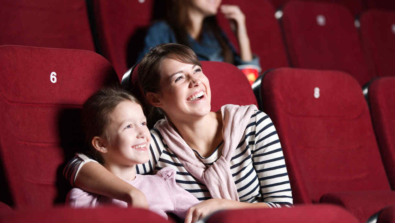Madre e hija riendo en la audiencia de un teatro