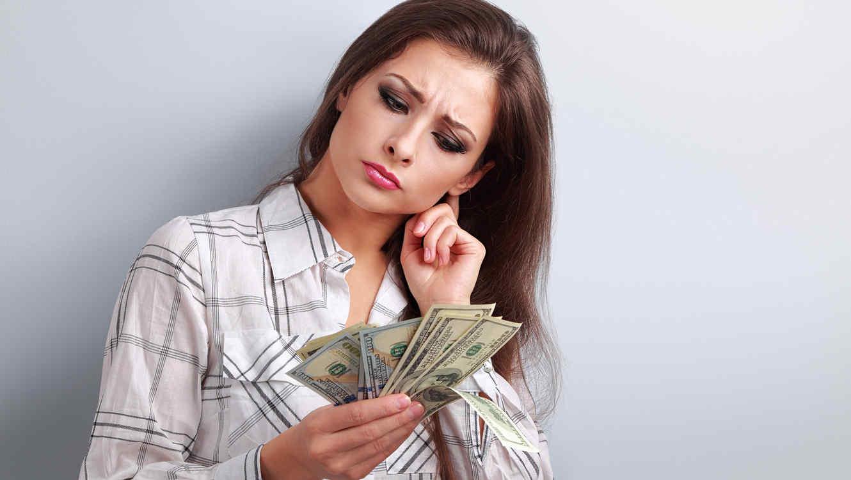 Mujer preocupada observa billetes