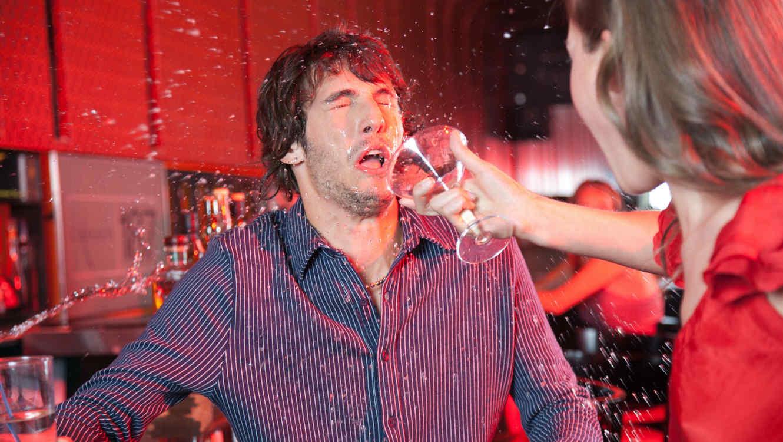 Mujer aventando un trago a la cara de un hombre