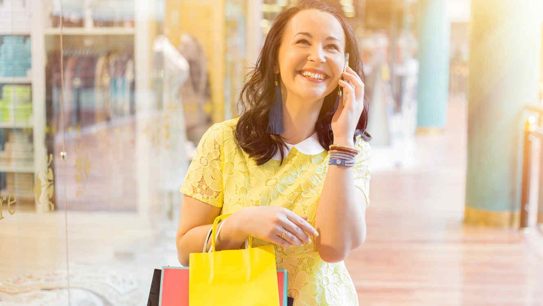 Mujer joven con bolsas de compras y usando el móvil