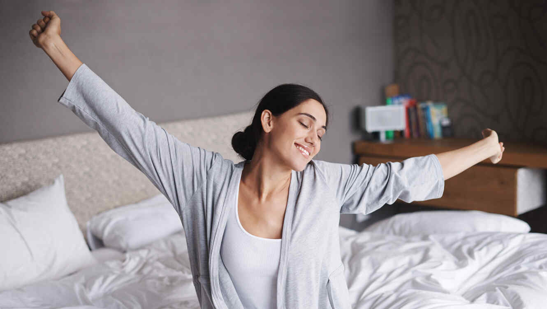 Mujer estirándose en la cama