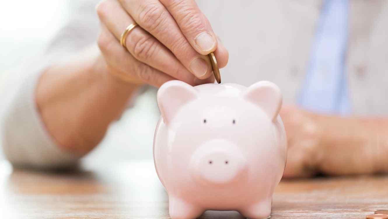 Mujer mayor poniendo moneda en una alcancía