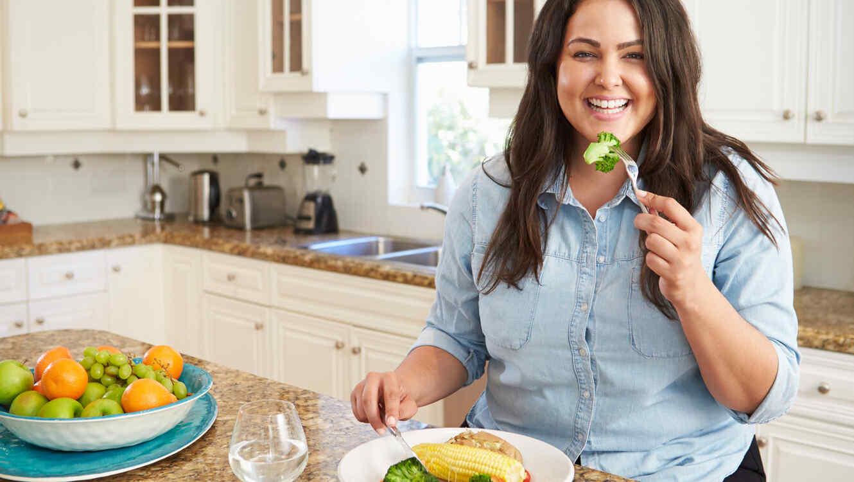 Mujer con sobrepeso comiendo saludable