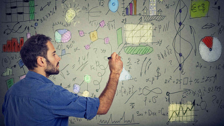 Hombre haciendo cálculos financieros frente a una pizarra