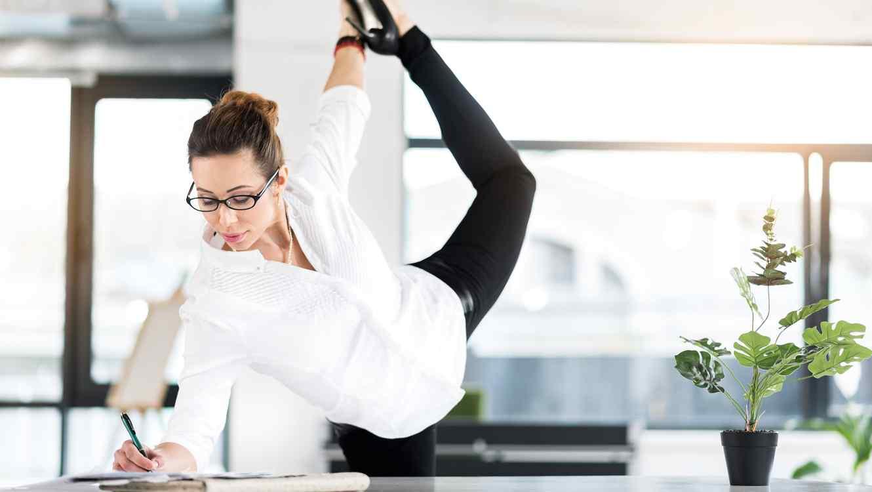 Mujer en oficina trabajando y elongando
