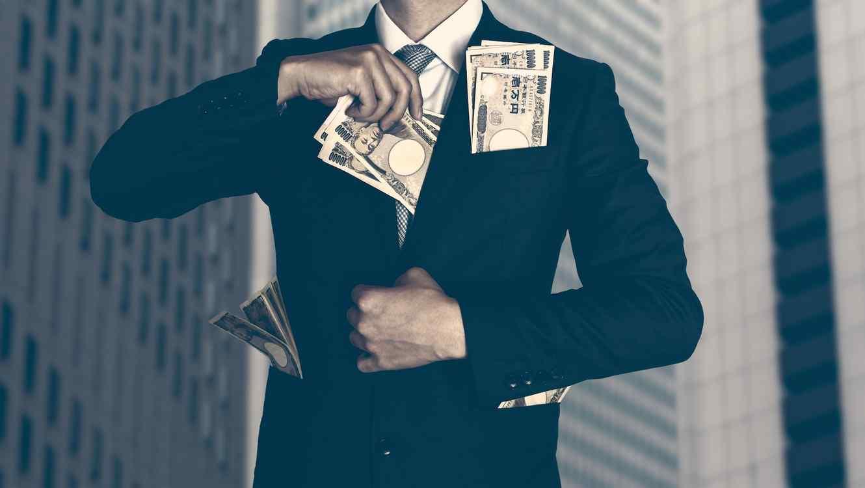Hombre de traje guardando billetes