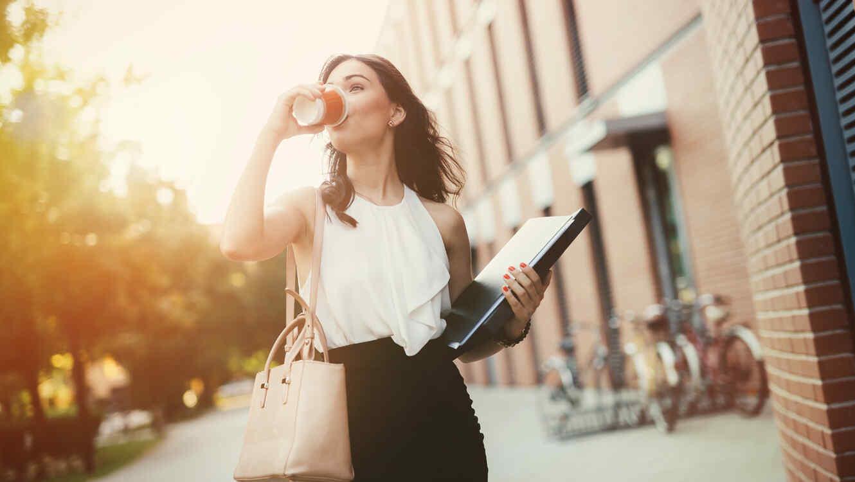 Mujer de negocios camina con café
