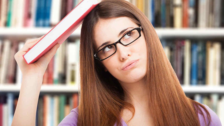 Retrato de una estudiante distraída con un libro en la biblioteca