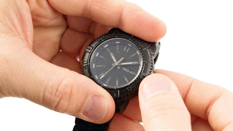 Persona cambiando la hora de su reloj