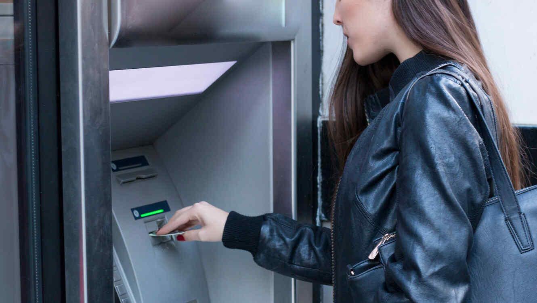 Mujer joven en el cajero automático
