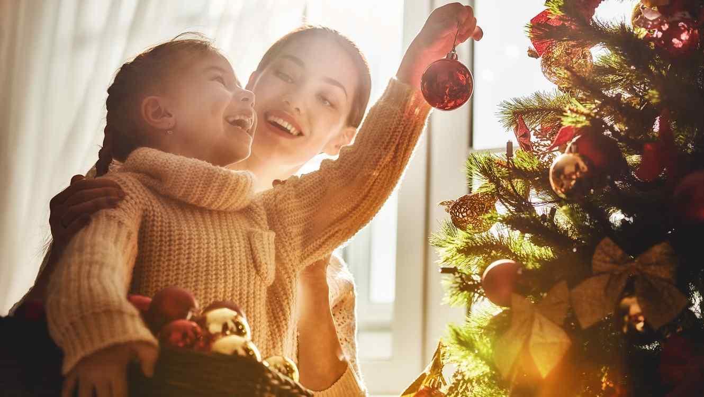 Madre e hija decorando árbol de Navidad