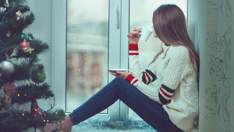 Mujer mirando cómo nieva por la ventana