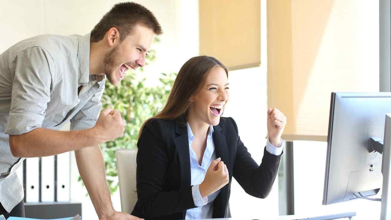 Mujer y hombre festejando frente a computadora