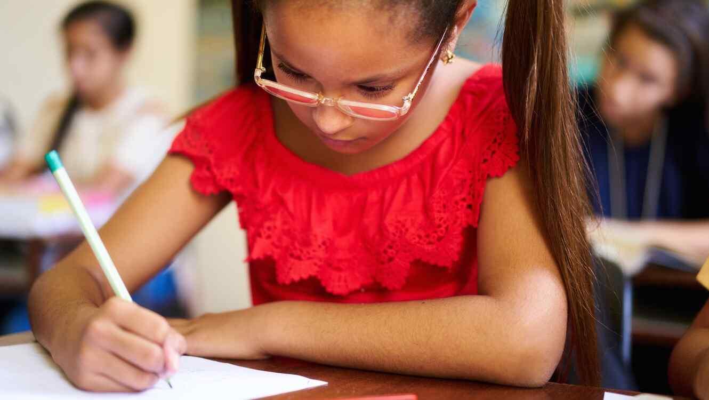 Niña con gafas escribiendo con lápiz