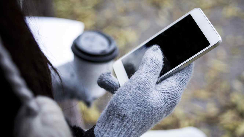 Mujer con guantes usando smartphone