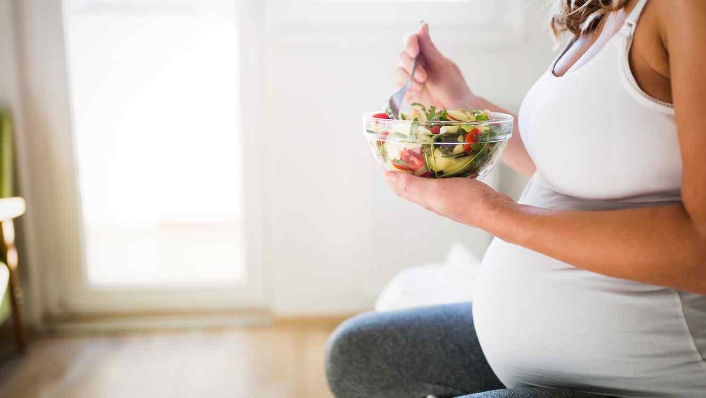 Mujer embarazada comiendo ensalada