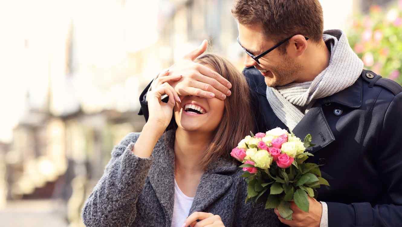 Hombre con flores tapando los ojos de mujer