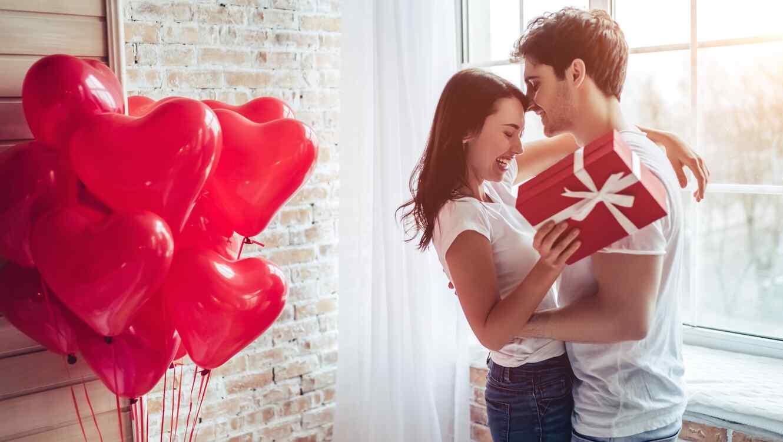 Pareja enamorada con regalo y globos