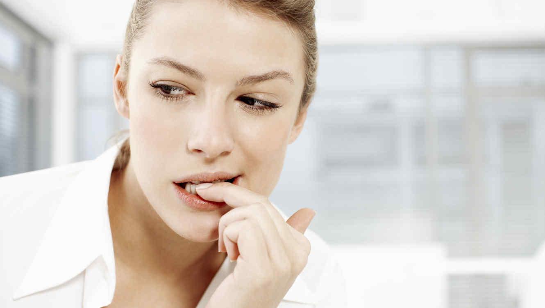 Mujer mordiendo sus uñas