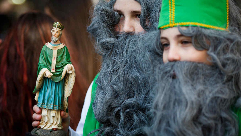 Niños disfrazados, con una estatua de San Patricio