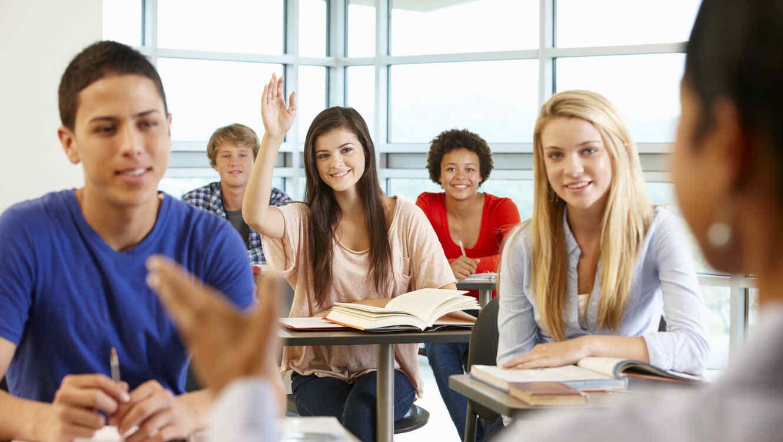 Estudiante de secundaria levantando la mano en clase