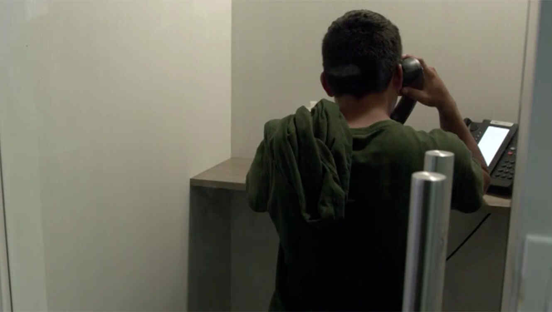 Un niño indocumentado habla por teléfono en el refugio Casa Padre en Texas
