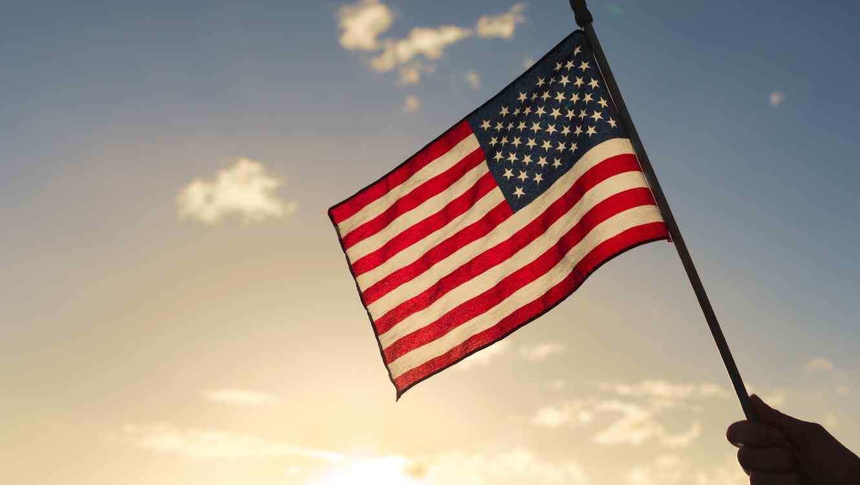 Mano sosteniendo bandera de EEUU