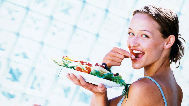Mujer sosteniendo un plato con verduras