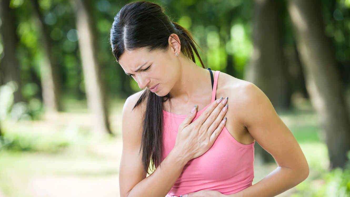 Mujer haciendo ejercicio, con dolor de pecho