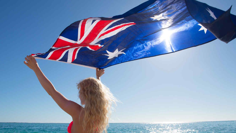Mujer rubia en la playa, con bandera australiana
