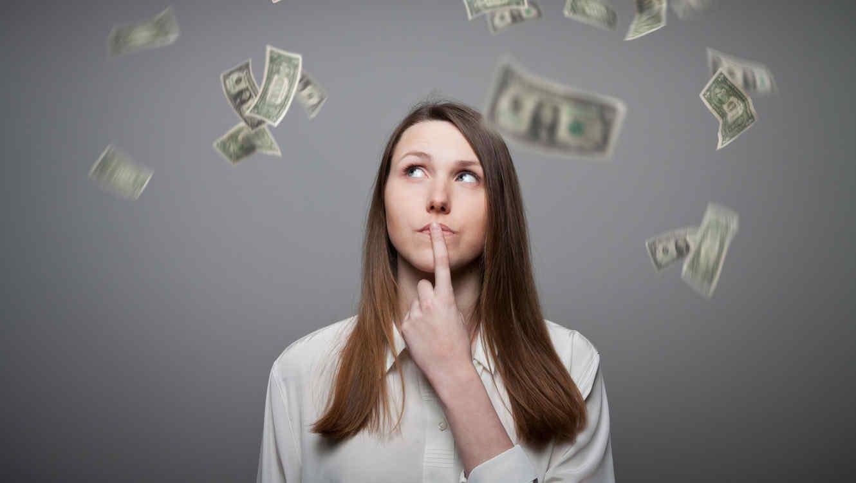 Mujer pensativa entre billetes volando