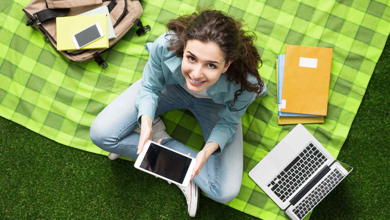 Mujer joven sentada en el césped, estudiando