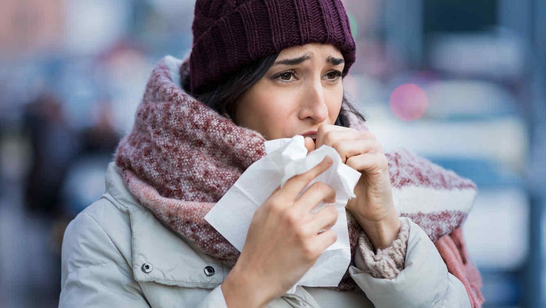 Mujer engripada, con tos y congestión