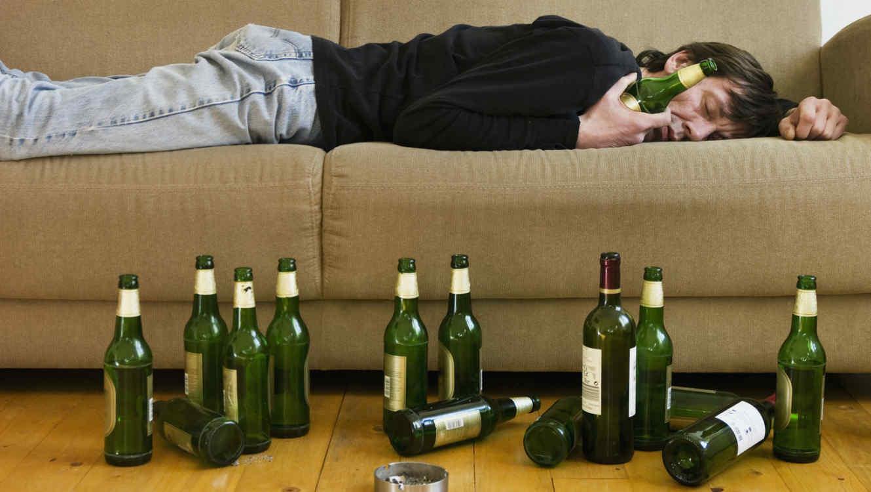 Hombre dormido con botellas de alcohol