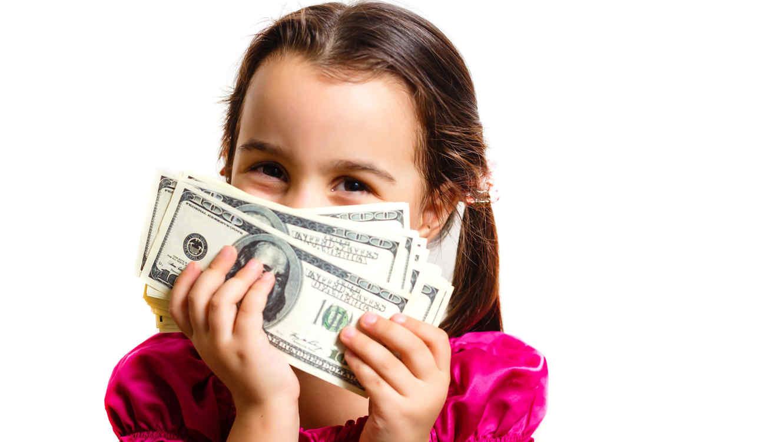 Niña feliz con dólares en la mano