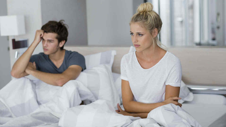Pareja discutiendo en una cama