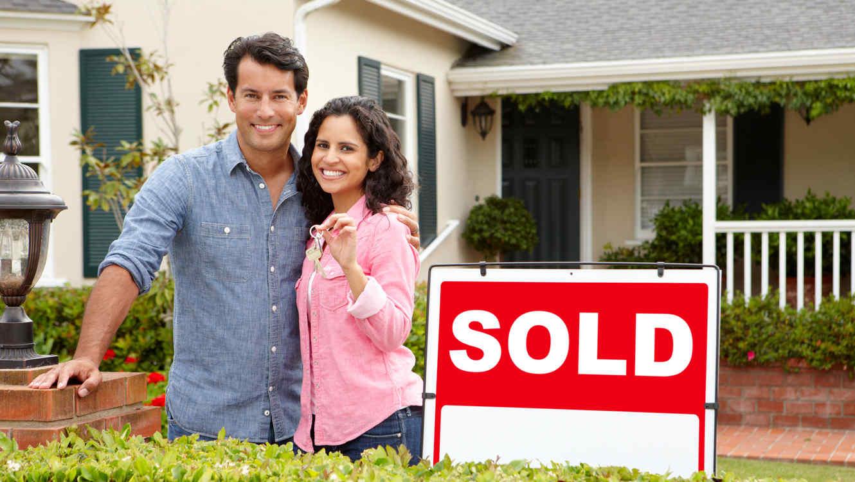 Pareja hispana frente a una casa vendida