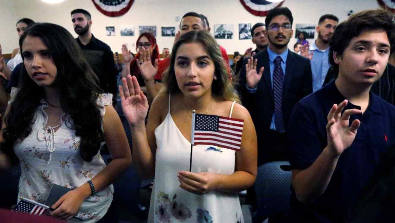 Ericka Ames, centro, de Nicaragua, recita el Juramento de Lealtad en  una ceremonia de naturalización en agosto de 2018, en Miami.