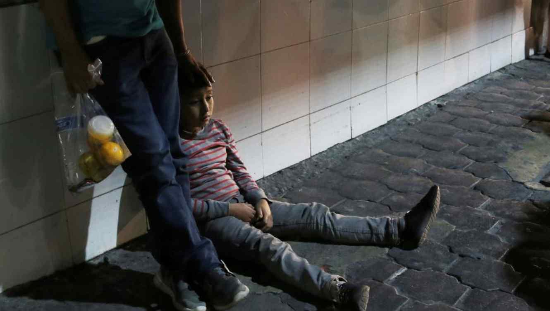 Foto del 18 de julio de 2019, un niño migrante y su padre luego de que las autoridades migratorias mexicanas los trasladaran en autobús desde Nuevo Laredo, en la frontera con Estados Unidos, a Monterrey.