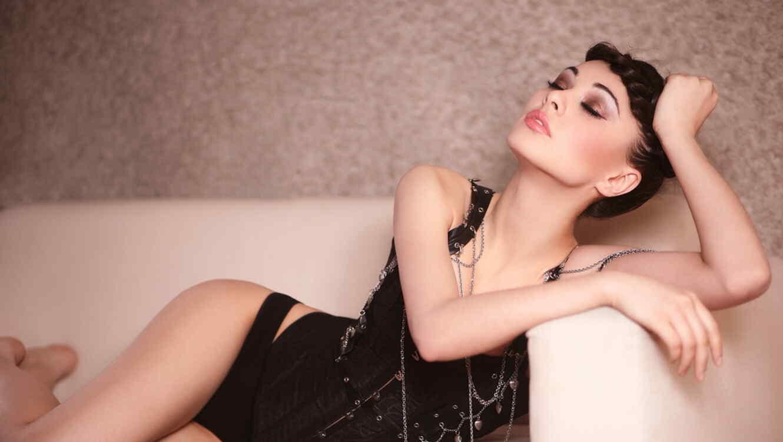 Modelo usando un corset waist training recostada en sofá