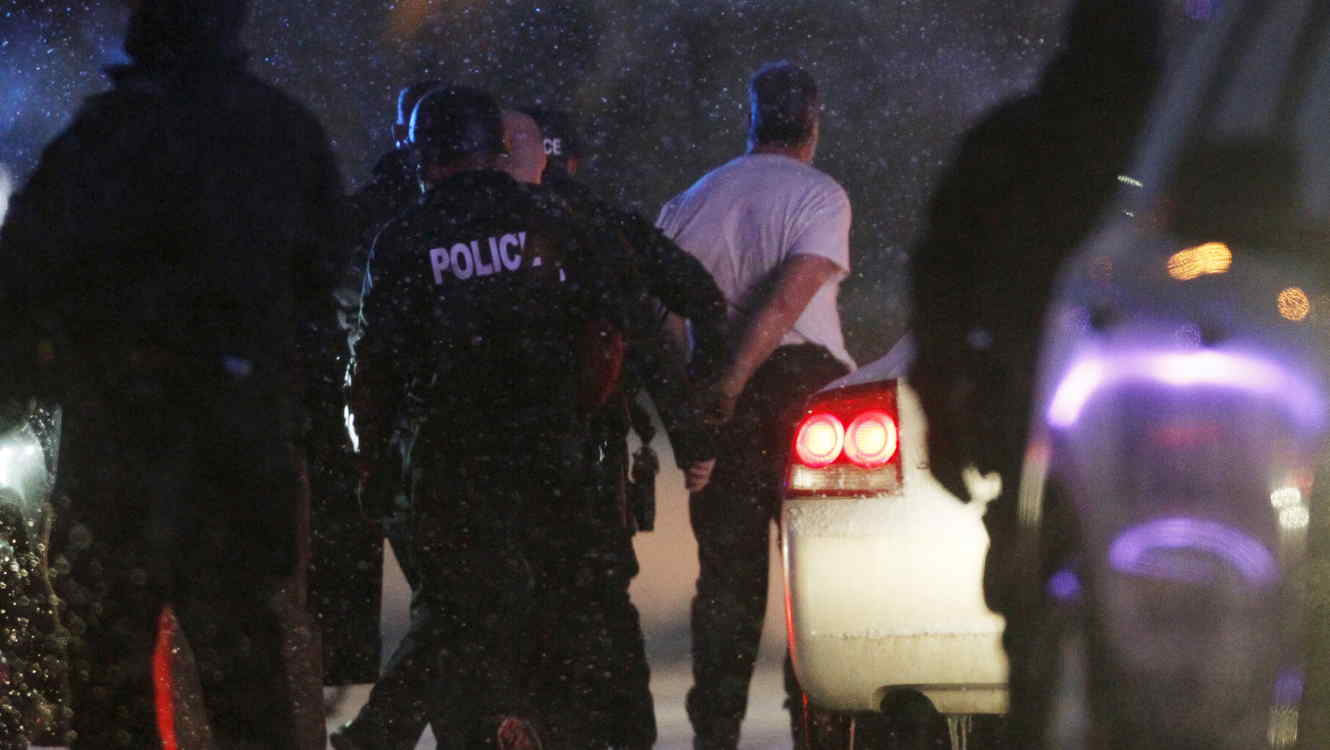 The handcuffed suspected gunman at the Planned Parenthood clinic is moved to a police vehicle in Colorado Springs, Colorado