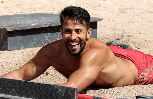 Tommy sonríe tirado en la arena