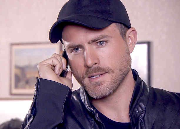 Erik Hayser con gorra negra hablando por teléfono en Los Miserables