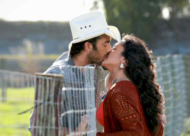 Aarón Díaz y Ana Lorena Sánchez besándose sobre una reja en Tierra de Reyes