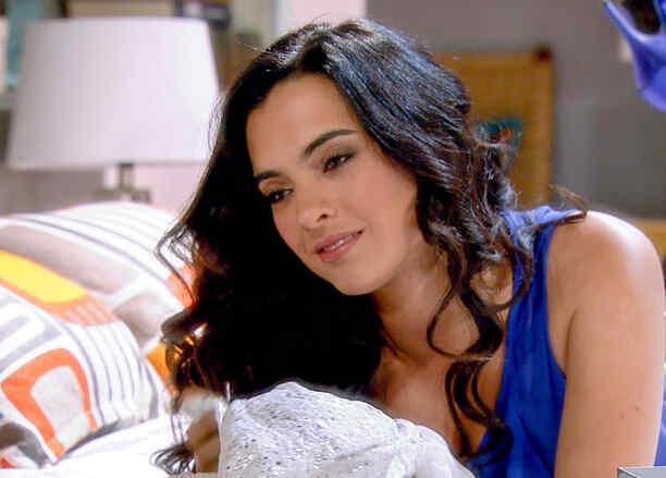 Scarlet Gruber acostada en la cama sonriendo en Tierra de Reyes
